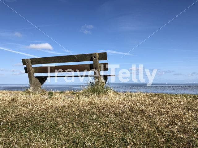 Bench on a dike at the wadden sea around Zurich in Friesland The Netherlands