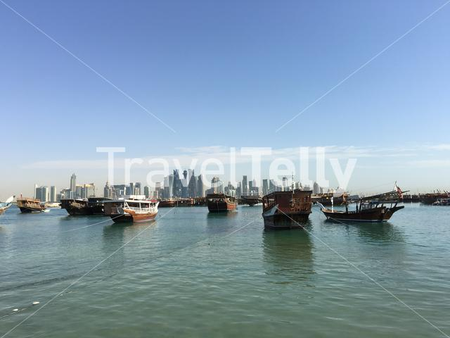 Traditional Dhow, Arab sailing vessels in the Dhow Harbour with the Doha skyline at the background in Qatar