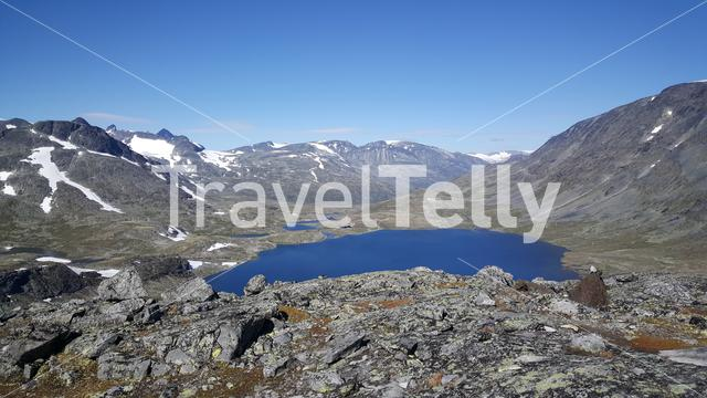Lake in front of mountains with snow in Jotunheimen National Park Norway