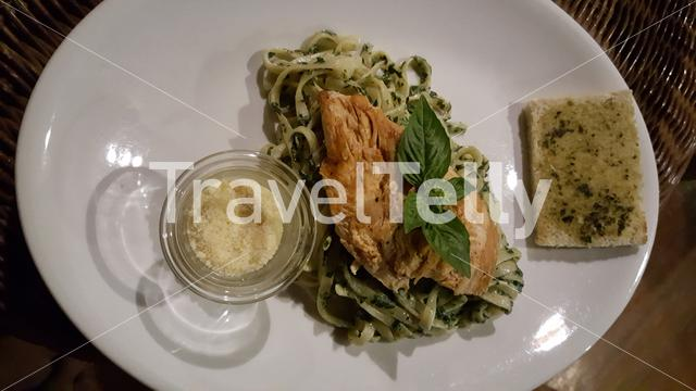 Pesto with chicken and cheese on white plate