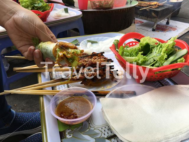 Pork skewer/ grilled pork wrapped in rice paper and vegetables in Hoi An Vietnam