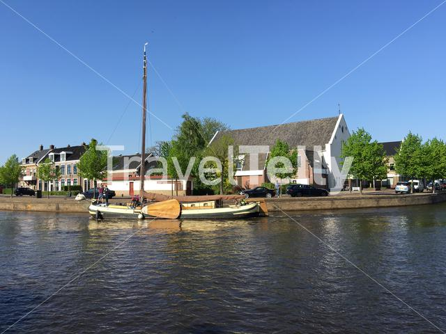 Skutsje sailing through the Prinsengracht with the waterpoort in the background in Sneek, Friesland The Netherlands