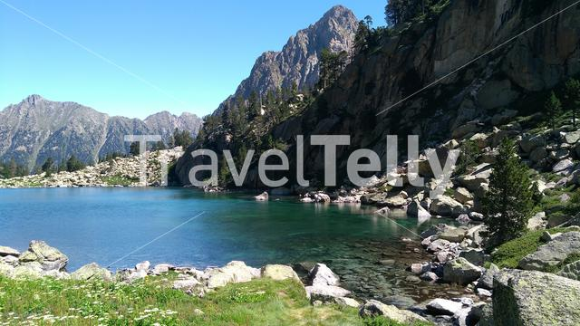 Crystal clear lake in Aigüestortes national park. Behind, one of the two peaks of els Encantats.