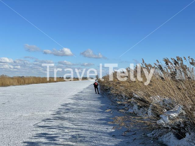 Man ice skating on a frozen canal in Friesland The Netherlands