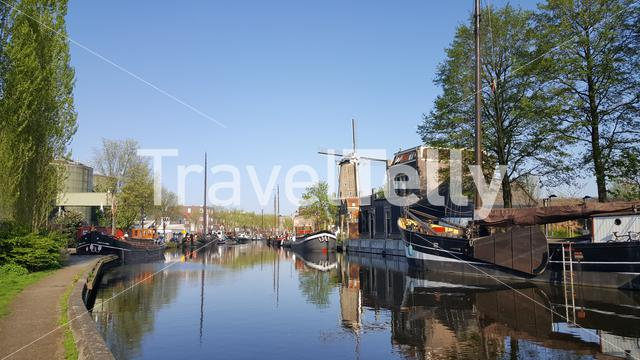 Dutch canals with windmill and boats in City of Gouda, The Netherlands