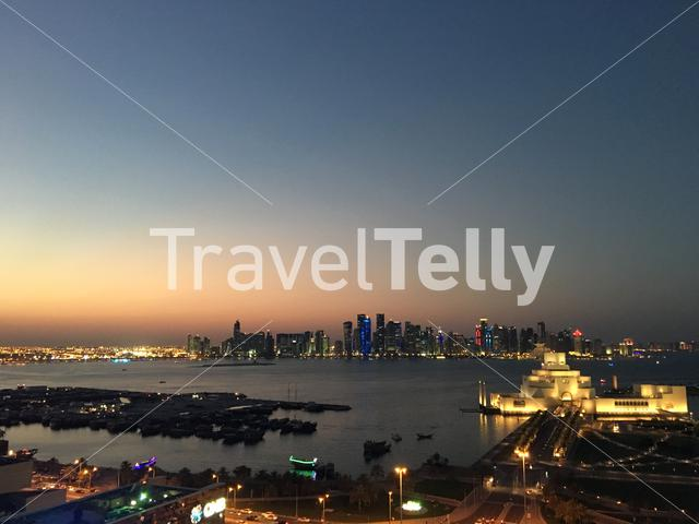 The Museum of Islamic Art on the Corniche with the Doha skyline during sunset