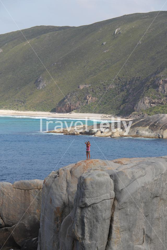 Girl taking a photograph at the Gap a stone formation in Torndirrup National Park Albany Western Australia