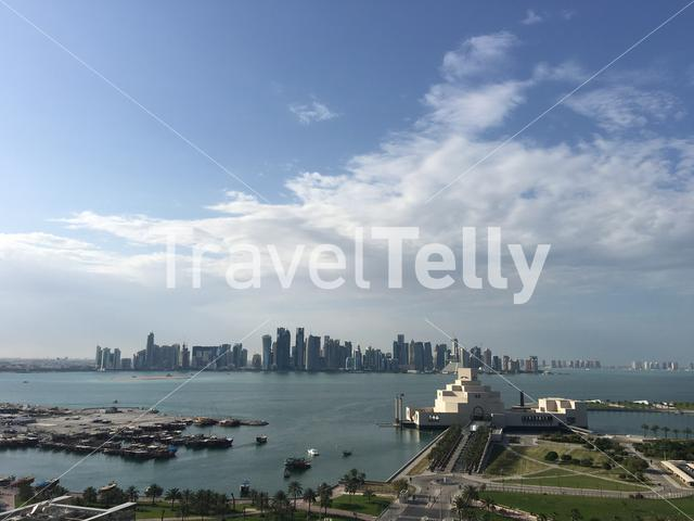 The Museum of Islamic Art on the Corniche with the Doha skyline in Qatar