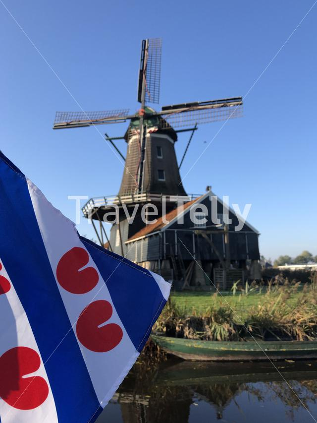 Frisian flag in front of the windmill in IJlst during autumn in Friesland, The Netherlands