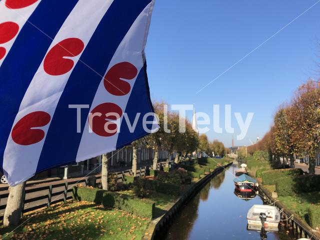 Frisian flag at a canal in IJlst during autumn in Friesland, The Netherlands