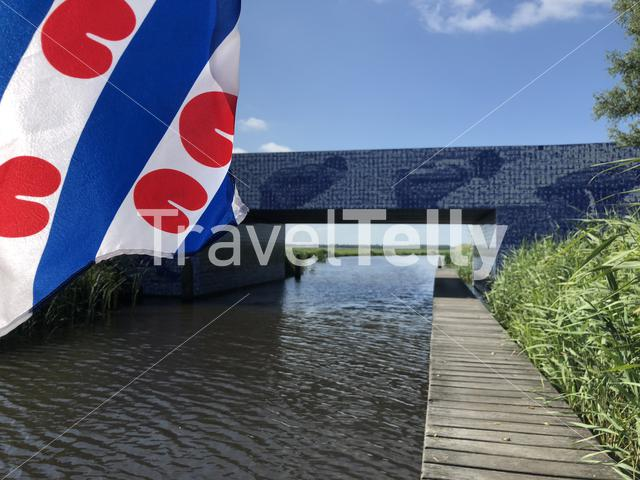 Frisian flag with the Elfstedenmonument a bridge over the Murk river in Friesland The Netherlands