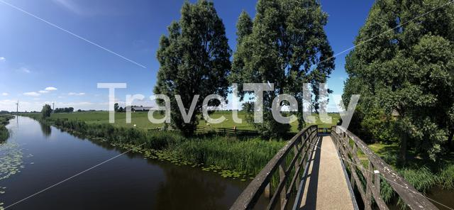 Panorama from a bridge over a canal in between Bartlehiem and Aldtsjerk in Friesland, The Netherlands