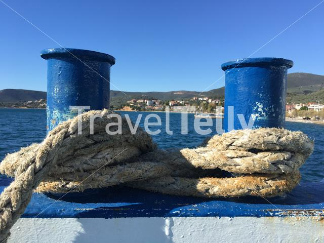 Bollard with a rope at a ferry leaving Glyfa Greece