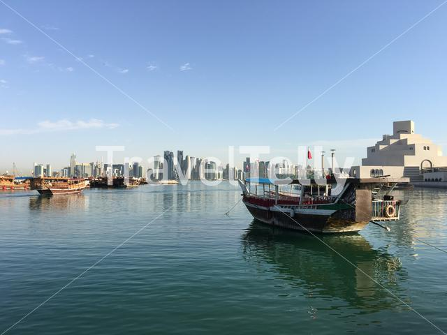 The Museum of Islamic Art on the Corniche with a traditional Dhow, Arab sailing vessel in the Dhow Harbour in Doha Qatar