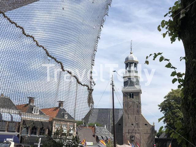 Tower of the reformed Church in lemmer behind a fishing net in Lemmer, Friesland The Netherlands
