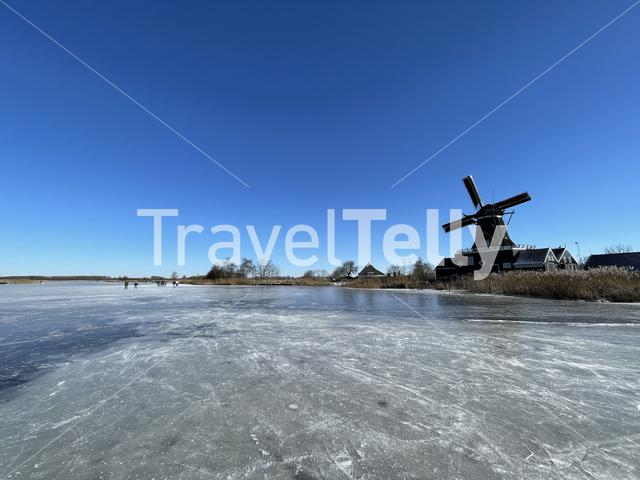 Frozen lake with the windmill from IJlst in Friesland The Netherlands