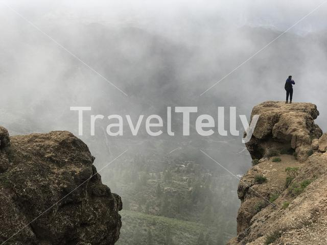 Man taking a picture at the Roque Nublo a volcanic rock on the island of Gran Canaria