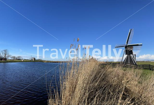 Windmill next to a canal on a winter day around Akkrum in Friesland The Netherlands
