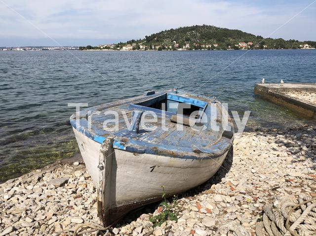 Boat on the beach with Otocic Osljak island on the background in Croatia
