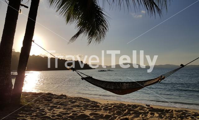 Hammock at tropical beach of Port Barton at sunset