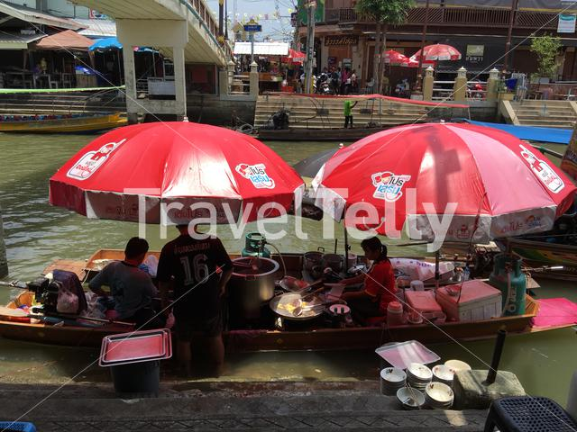 Preparing food at the Amphawa floating market in Thailand