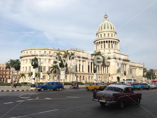 Classic cars in fornt of the El Capitolio National Capitol Building in Havana, Cuba