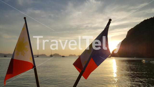 Sunset with national flags at El Nido beach, Palawan, Philipinnes
