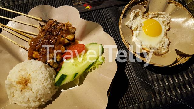 Fried egg, sate and rice on a paper plate