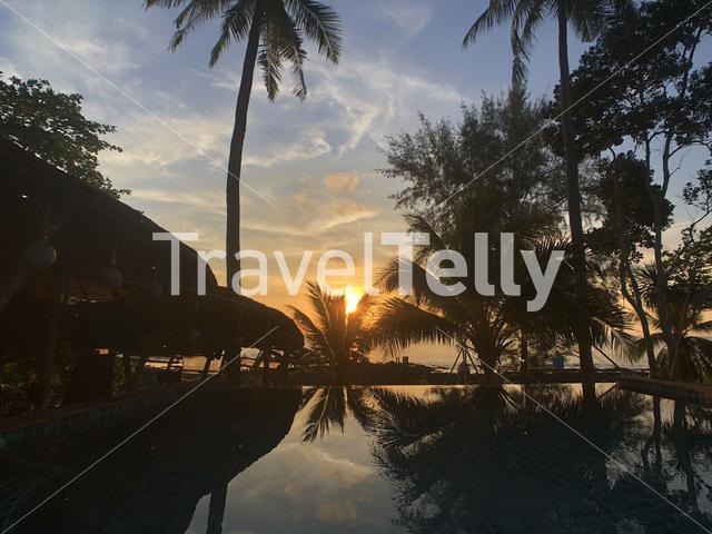 Sunset with palmtree reflection in a pool at Koh Lanta Thailand