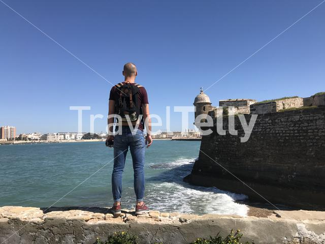 Man standing at the wall of the Castle of San Sebastian in Cadiz Spain