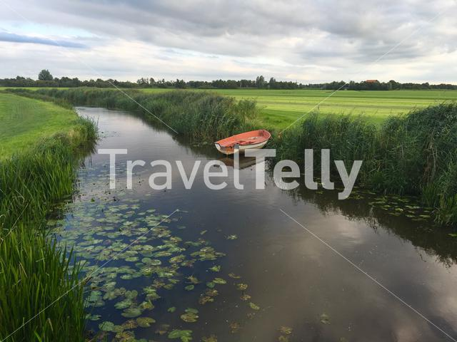 Small river with a boat in Friesland The Netherlands