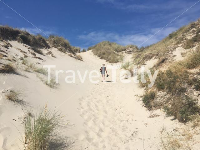 Woman walks on a sand dune towards the beach  on Terschelling island in The Netherlands