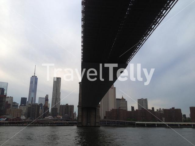 Freedom Tower and manhattan skyline from under the Brooklyn Bridge at the East River New York City
