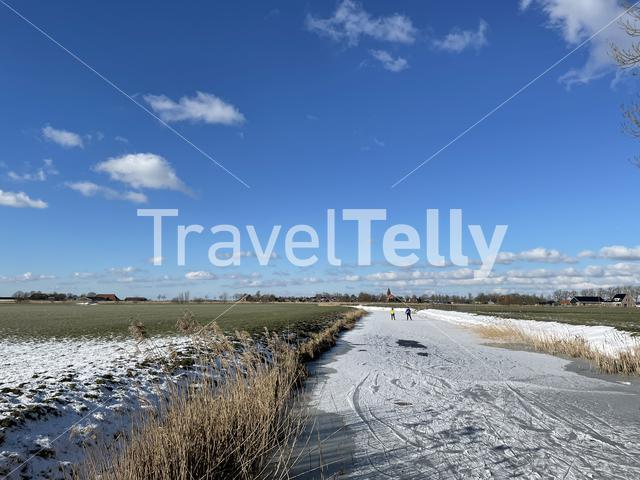 Couple ice skating on a frozen canal in Friesland The Netherlands