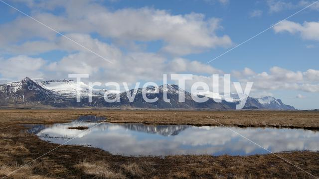 Snowy mountains landscape with reflection in a lake