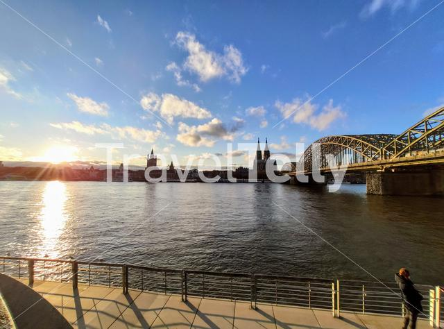 Sunset view of the Hohenzollern bridge across the Rhine river and Cologne cathedral