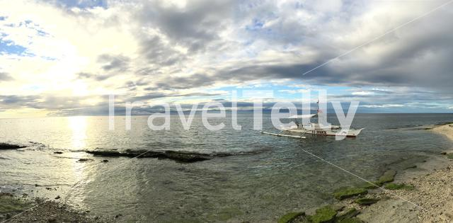 Panorama from a catamaran boat in the water during sunset at Balicasag Island in Bohol the Philippines