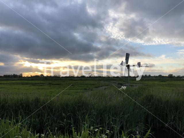 Cloudy sunset with a small windmill around Sneek, Friesland The Netherlands