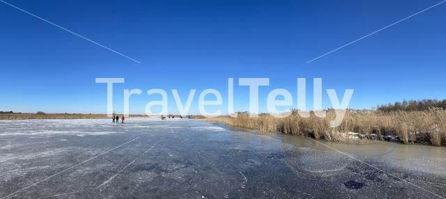 Panorama from people ice skating on a frozen lake around Sneek in Friesland The Netherlands