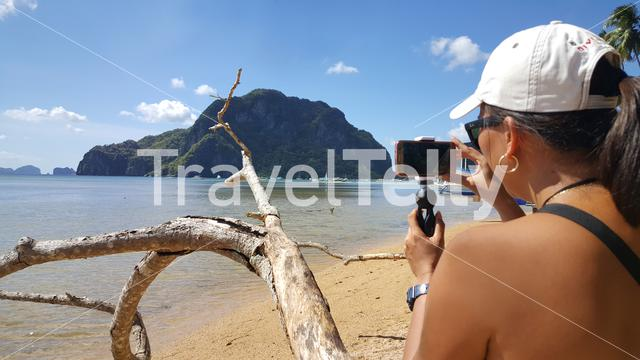 Philipina woman takes mobile photos from tropical islands of El Nido