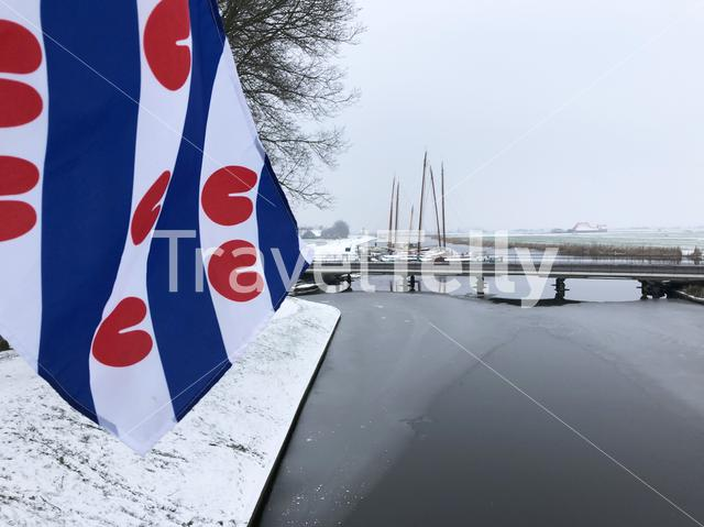 Frisian flag with skutsjes in the background during winter  in Sloten, Friesland, The Netherlands