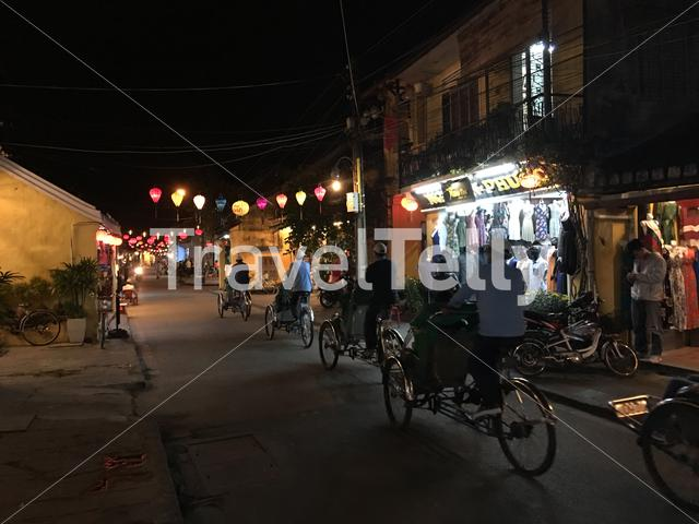 Toerist on a tricycle at night in the streets of Hoi an Vietnam