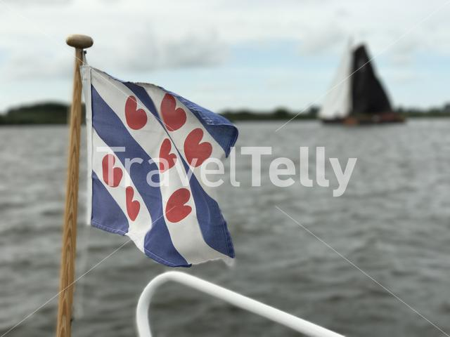 Frisian flag with a Skutsje at the Sneekermeer in Friesland The Netherlands
