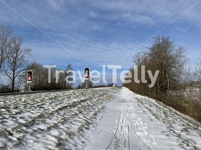 Snowy bicyle path towards the bridge over the Prinses Margriet canal in Friesland, The Netherlands