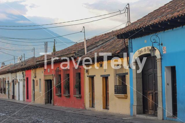 Façades of colorful houses in the streets of small town Antigua Guatemala with a partial view of Agua Volcano on the background