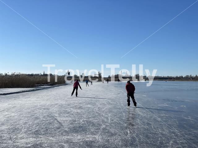 People ice skating on a frozen lake towards IJlst in Friesland The Netherlands