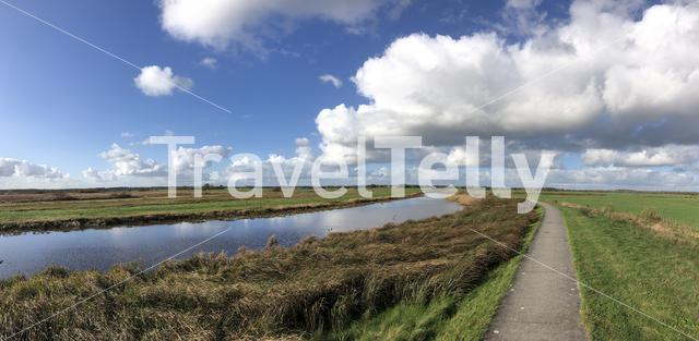 Panorama from a path through grassland towards Nieuwehorne in Friesland, The Netherlands