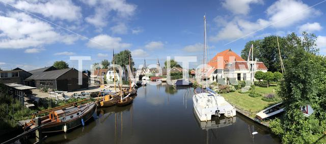 Panorama from a canal with wooden sailboats in Heeg, Friesland, The Netherlands