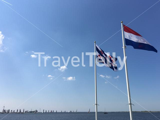 The Frisian and Dutch flag with Skutsjes in the background in Lemmer, Friesland The Netherlands