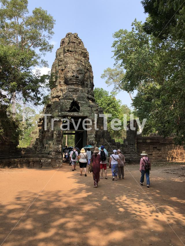 Big group of tourists walking through a gate around Ta Prohm Temple (tomb raider temple), Cambodia